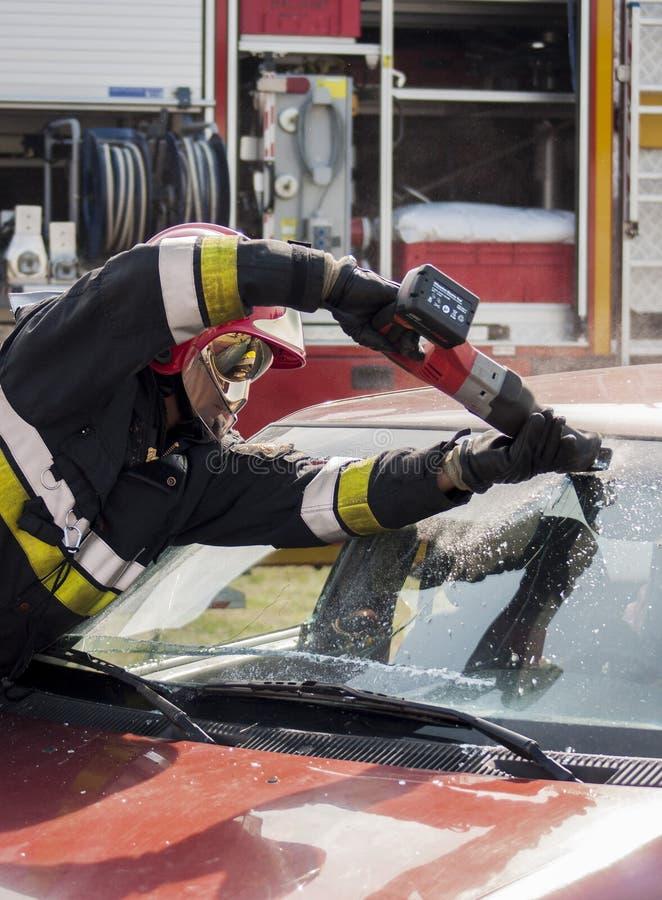 Brandman i handling på bilolyckan arkivfoto