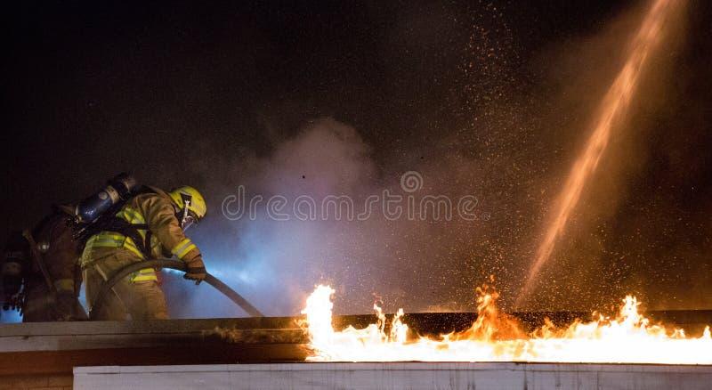Brandman i handling på taket arkivbild