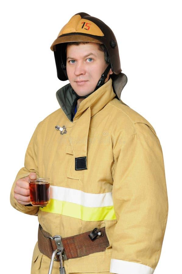 Brandman med en kupa av svart tea arkivbilder