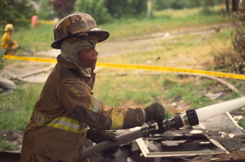 Brandman med ett hällande vatten för slang på en brand arkivfoto