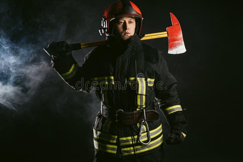 Brandman med hammare är inte rädd för fara och eld royaltyfria foton