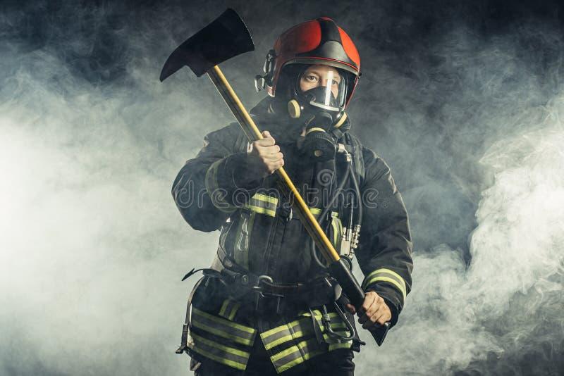 Brandman med hammare är inte rädd för fara och eld arkivbilder