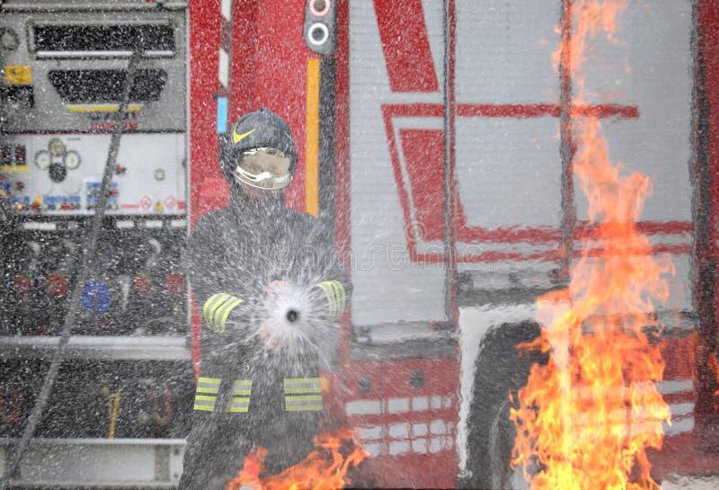 brandman med hjälmen och likformig i handling royaltyfria bilder