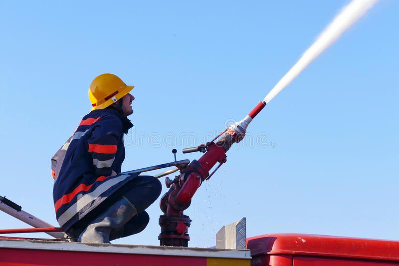 Brandman på en vattenkanon royaltyfri foto