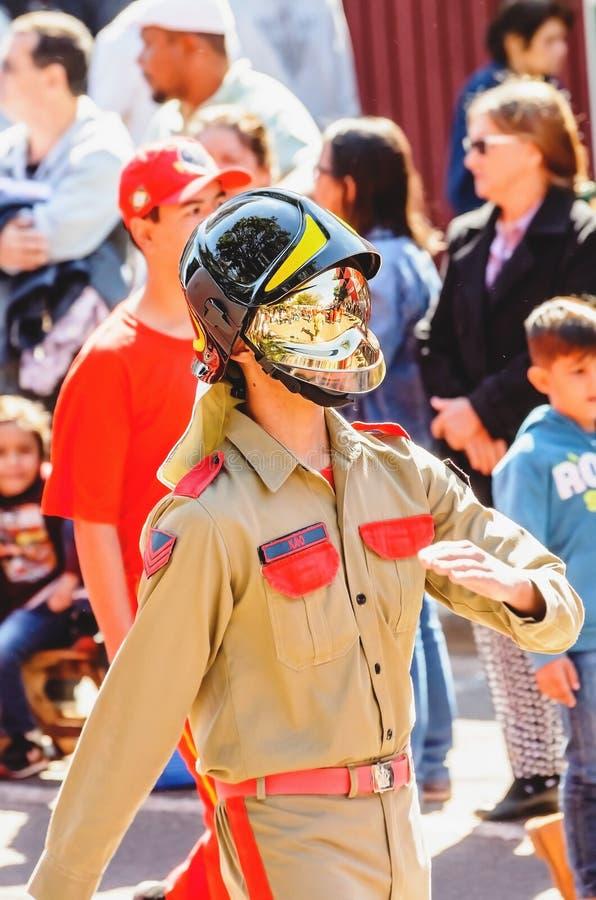 Brandman som bär en guld- hjälm som ståtar på berömmen arkivfoto