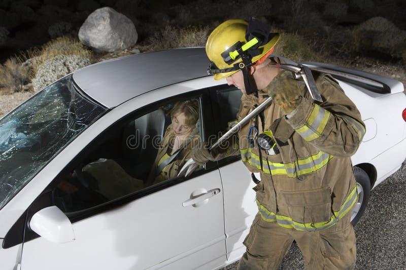 Brandman som försöker att öppna bils dörr fotografering för bildbyråer