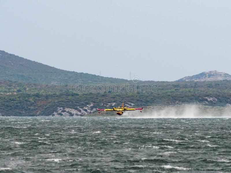 Brandmanflygplan, vattenbombplan, luftbehållare som tar vatten från t arkivbild