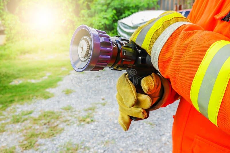 Brandmanhåll och att justera dysa- och brandslangen som besprutar högtryckvatten royaltyfri foto
