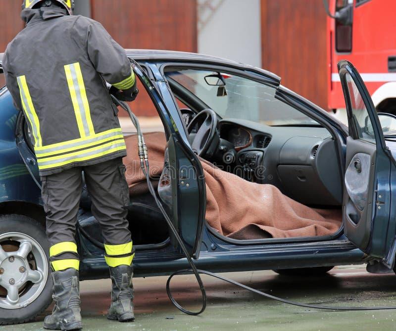 Brandmanlaget drar mannen som såras av bilen efter en väg a royaltyfri foto