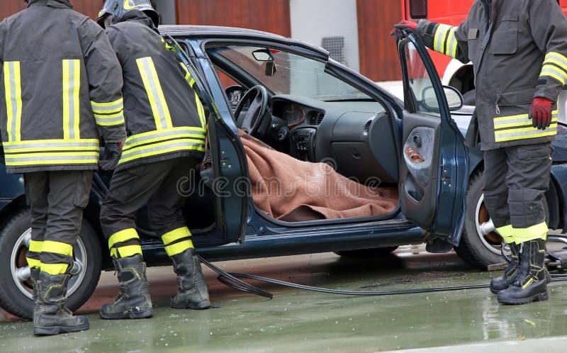 Brandmanlaget drar ut personen från inre bilen efter a royaltyfria bilder
