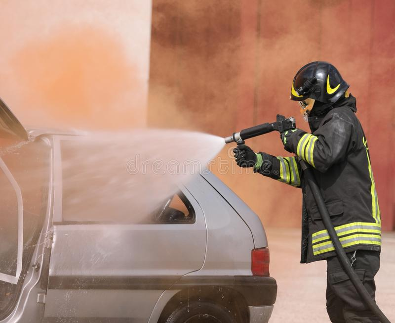 Brandmannen anv?nder skum under en v?golycka p? den brutna bilen royaltyfri fotografi