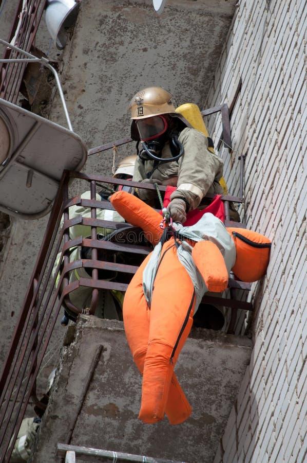 Brandmannen evakuerar attrappen för offer` s från balkongen av den hous bränningen arkivbilder