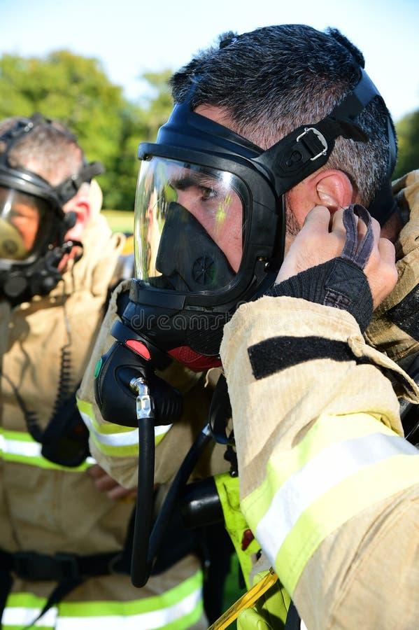 Brandmannen förbereder hans maskering för andningapparaturen på brandplatsen arkivbild