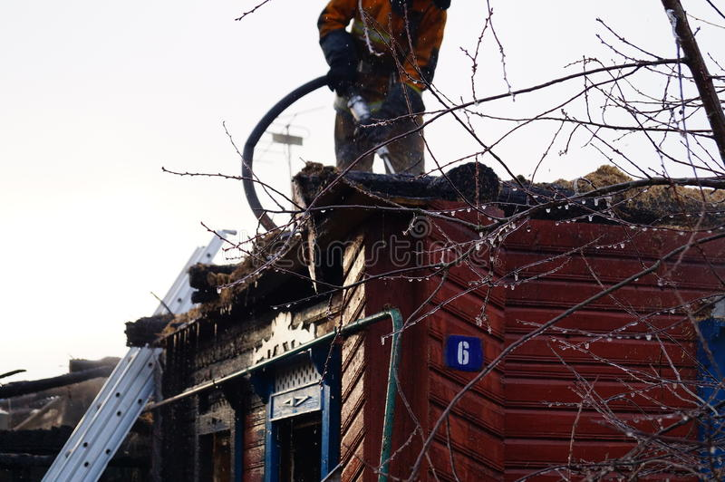 Brandmannen häller taket av trähuset efter brand - släcka royaltyfria bilder