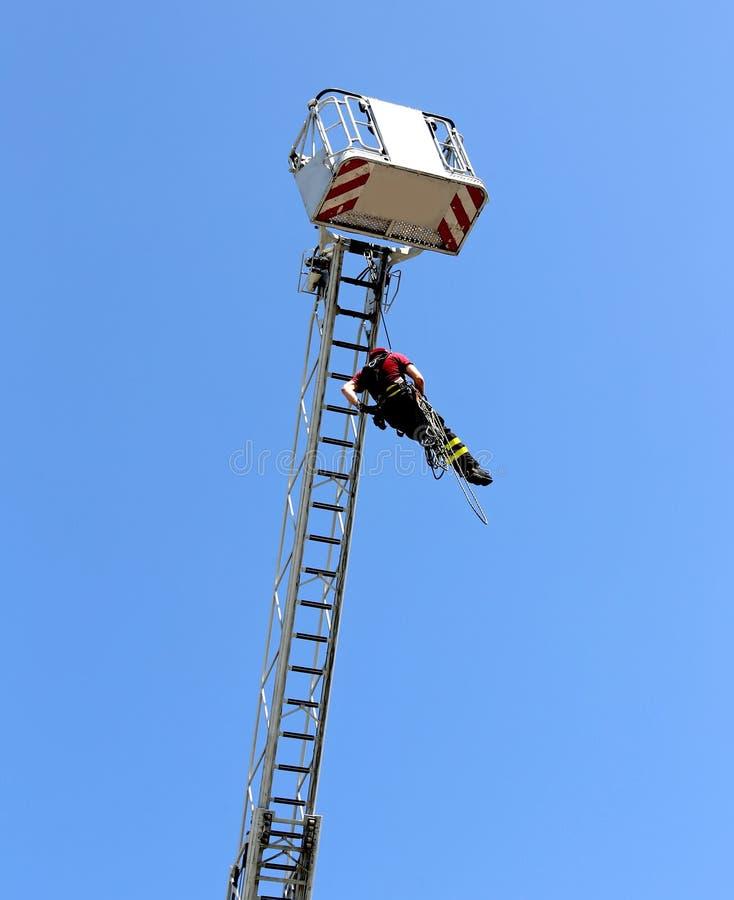 Brandmannen hängde repklättringen i firehousen royaltyfri bild