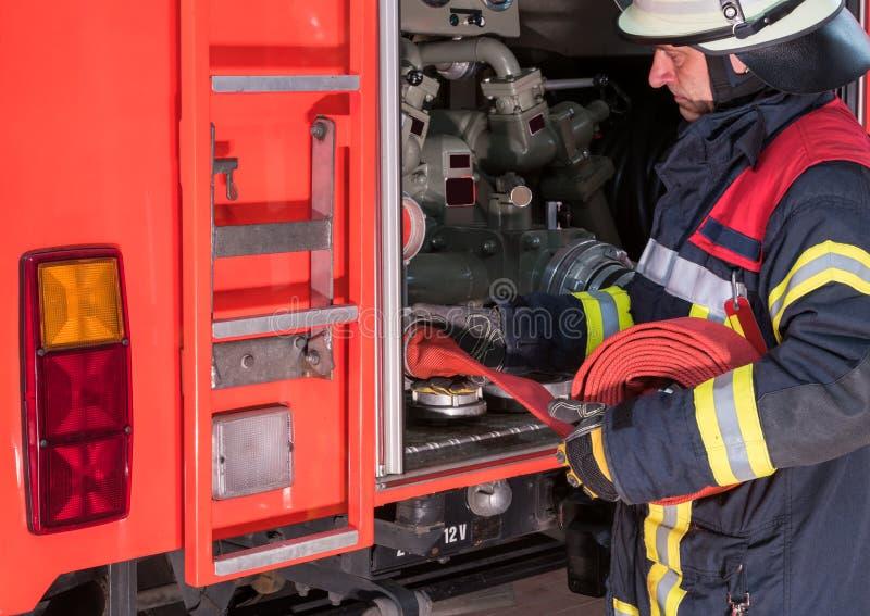 Brandmannen i handling förband en brandslang på brandlastbilen fotografering för bildbyråer