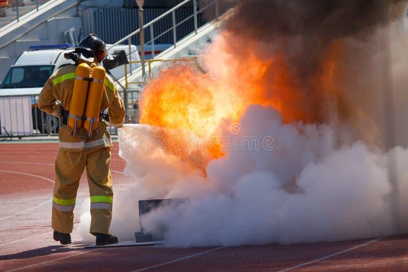 Brandmannen i utrustning släcker brand royaltyfri foto