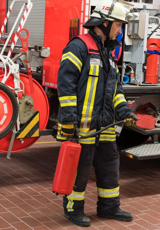 Brandmannen på brandlastbilen använde en brandsläckare royaltyfria bilder