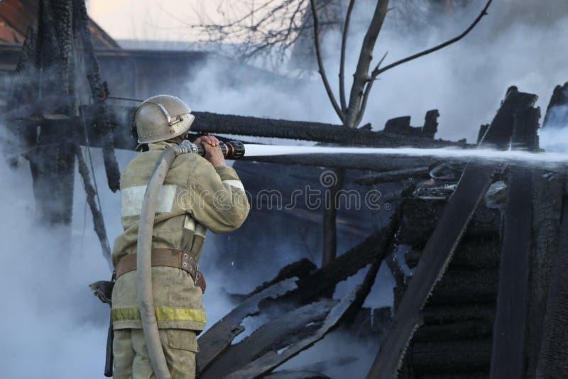 Brandmannen släcker branden E arkivbild