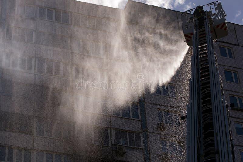 Brandmannen släcker en brand i en hyreshus från höjden av en brandkran royaltyfria foton
