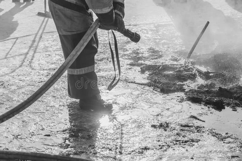 Brandmannen släcker med vatten royaltyfri fotografi