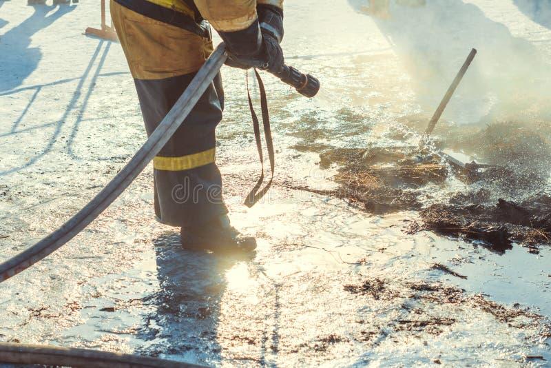 Brandmannen släcker med vatten fotografering för bildbyråer