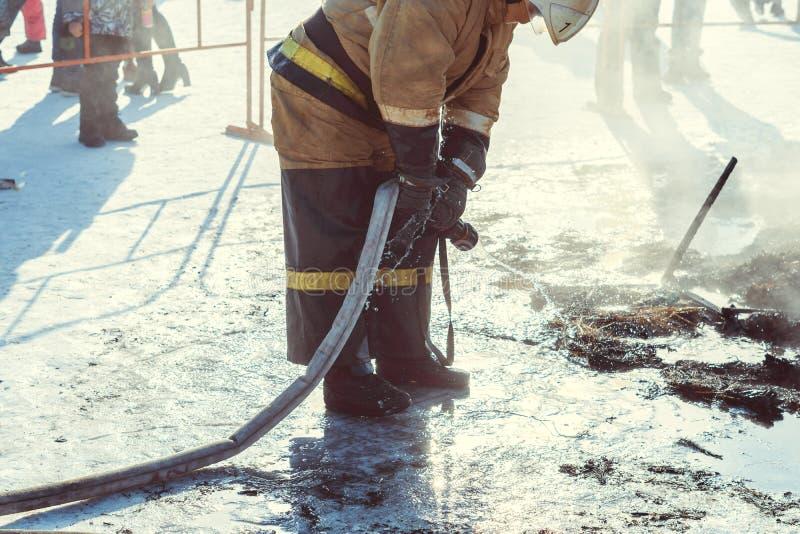 Brandmannen släcker med vatten arkivbilder