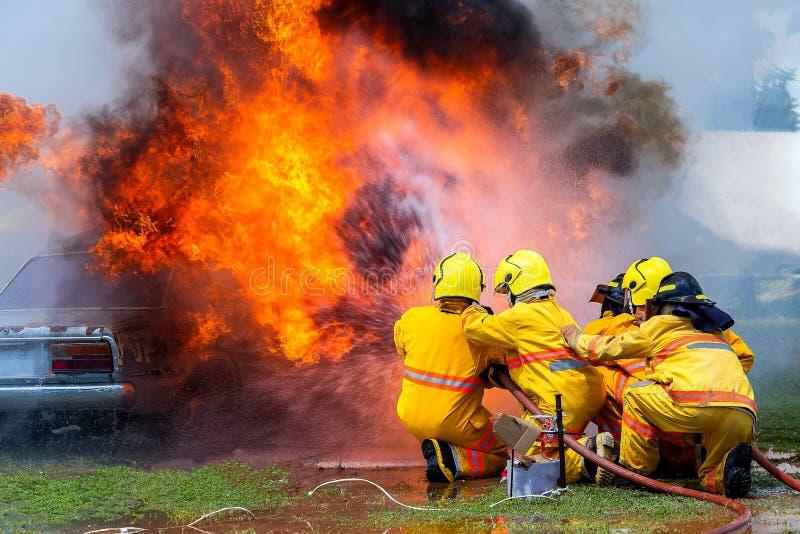 Brandmannen som använder vatten- och eldsläckarebilen, är på brand, brandmannen som använder eldsläckaren och vatten från slangen arkivbild