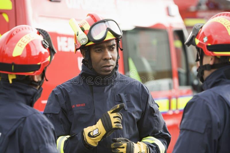 brandmannen som ger hans anvisningar, team till royaltyfria bilder