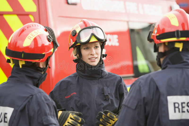brandmannen som ger henne anvisningar, team till royaltyfri fotografi