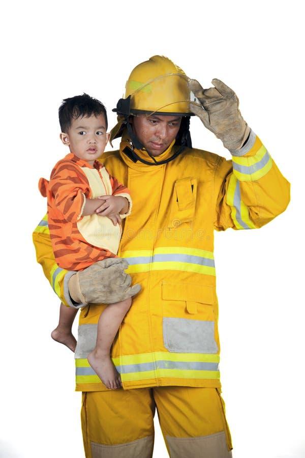 Brandmannen sparar barn från brand royaltyfria foton