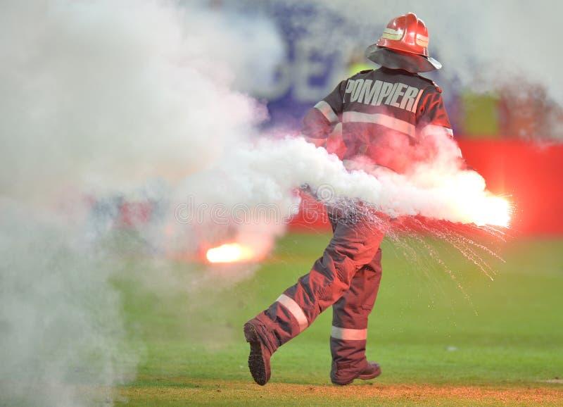 Brandmannen tar bort signalljus från fotbollgraden royaltyfri bild