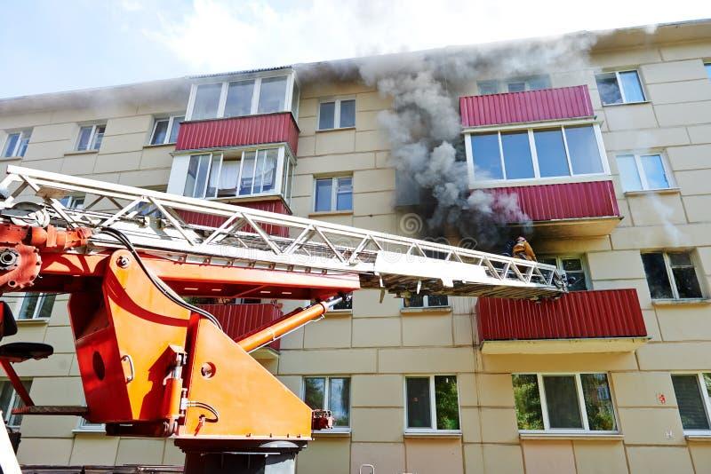 Brandmannen under släcker en brand royaltyfri fotografi
