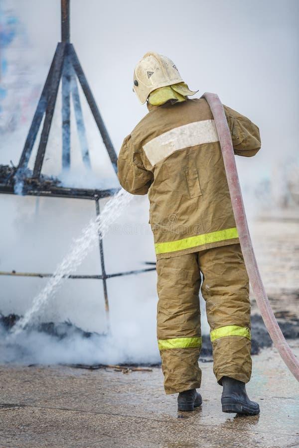 Brandmannen, vid hjälp av vattenposten med vatten, släcker restna av brand i röken royaltyfri fotografi