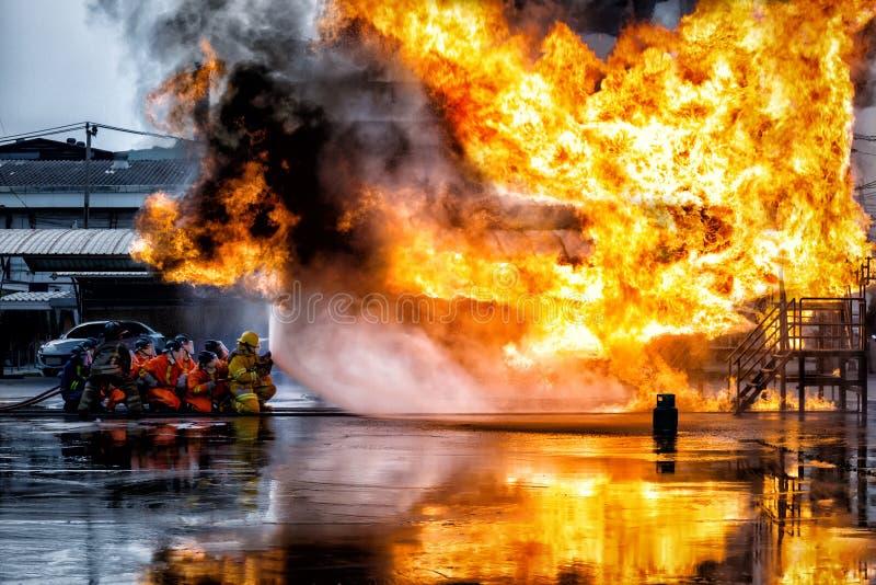 Brandmanutbildning , brandman som använder vatten och eldsläckaren till f arkivfoton