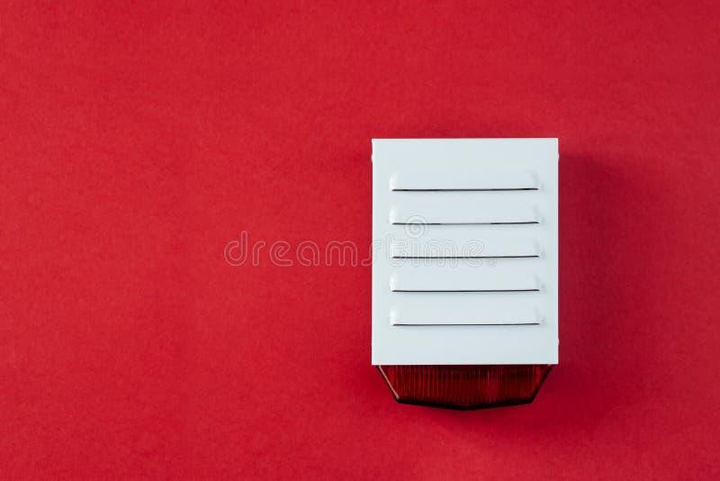 Brandsäkerhetssystem på en röd bakgrund av ett kopieringsutrymme royaltyfria foton