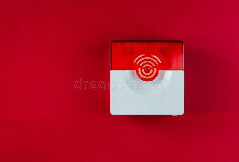 Brandsäkerhetssystem på en röd bakgrund av ett kopieringsutrymme fotografering för bildbyråer