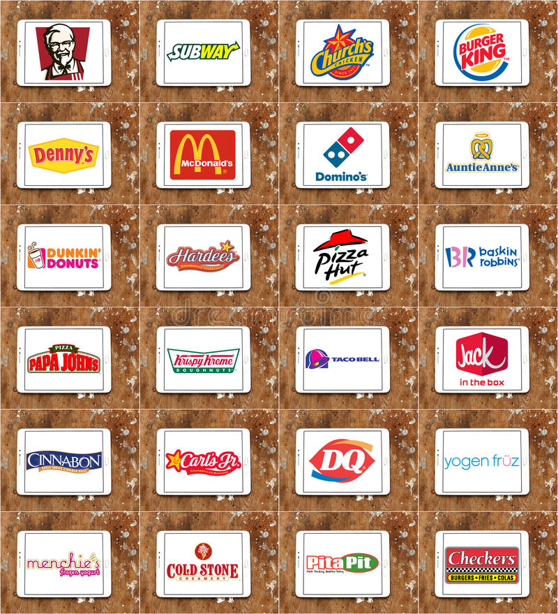 Brands and logos of top food franchises. Collection of logos and brands of top famous food franchises and restaurants on white tablet on rusted wooden background