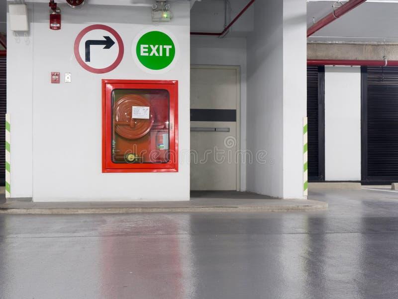 Brandsläckare med olika typer av brandsläckare som lokaliseras i dörren för brandflykt i parkeringsplatsen royaltyfri foto