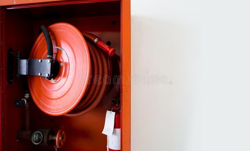 Brandsläckare med olika typer av brandsläckare som lokaliseras i den vita väggen Kopieringsutrymme för text och innehåll royaltyfri bild