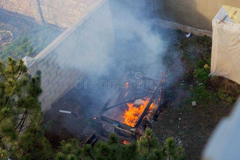 Brandspolar över en bränd byggnad En hög av kol på platsen för en bränd byggnad Ljusa lågor, flygande aska av brinnande trä royaltyfri bild