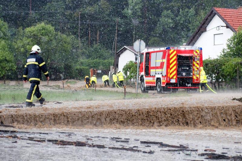 Brandstationen rusar för att rädda när floder slår byn i Europa efter hällregn royaltyfri fotografi