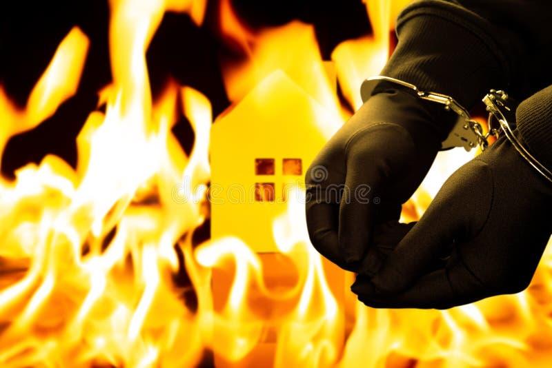 Brandstichter in handcuffs met het branden van huis op achtergrond royalty-vrije stock fotografie