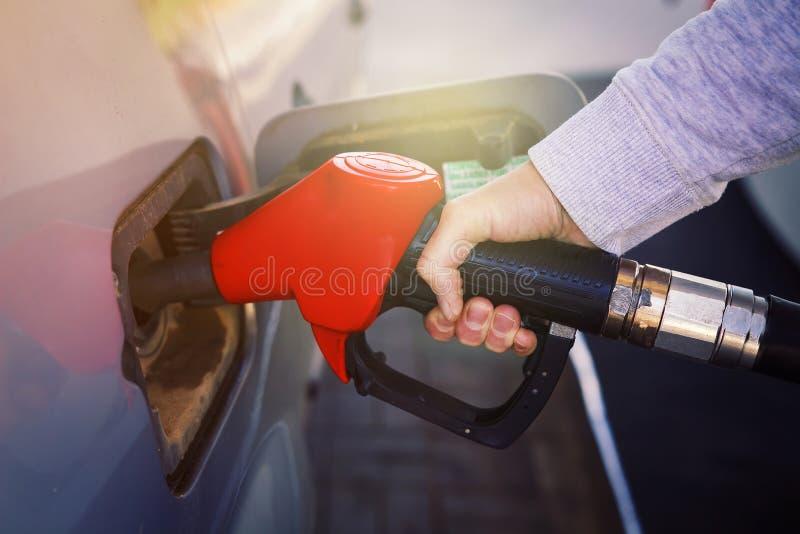 Brandstofauto bij benzinestation Pompend gas bij benzinepomp Close-up van brandstof van de mensen de pompende benzine in auto bij stock foto