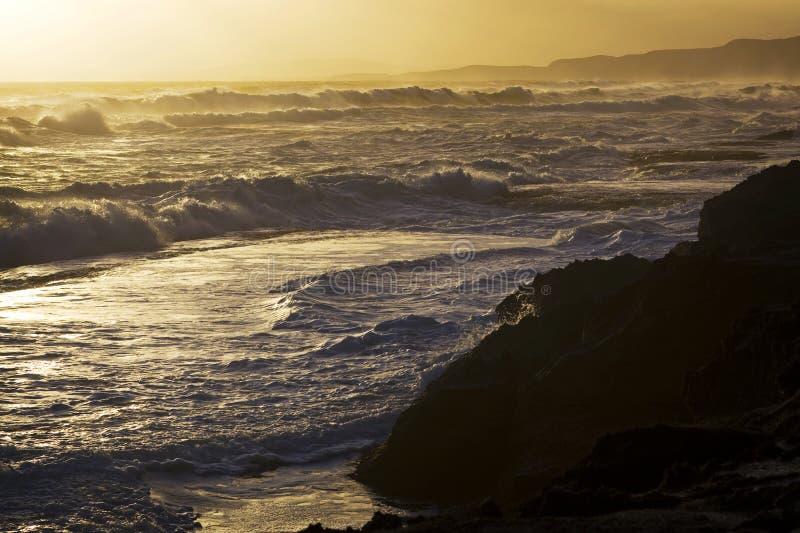 Brandung auf Strand am Sonnenuntergang stockfoto