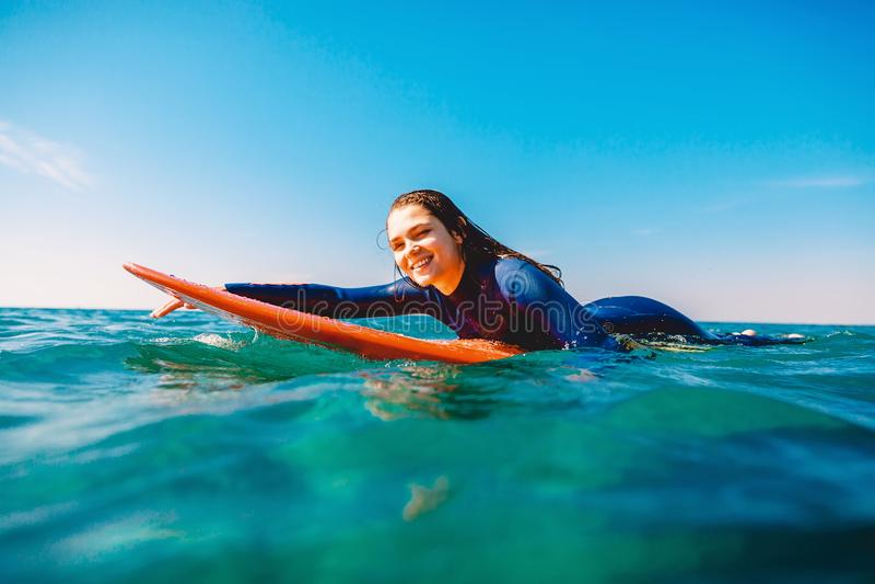 Brandungsmädchen ist, rudernd lächelnd und auf dem Surfbrett Frau mit Surfbrett im Ozean Surfer und Ozean stockfotografie