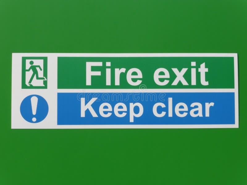 Brandutgång och klart tecken för uppehälle på en grön bakgrund royaltyfria bilder