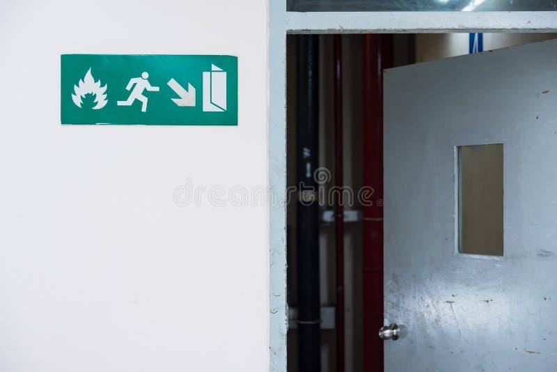 Brandutgången undertecknar in vägen för den nöd- utgången för flygplatsterminalen Thaila royaltyfri fotografi