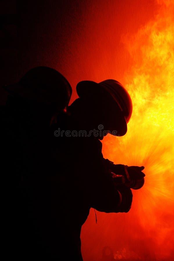 Brandvechter bij brand stock afbeeldingen