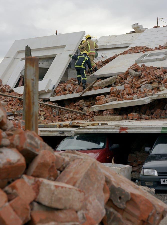 Brandvechters die de bouwinstorting zoeken stock foto's